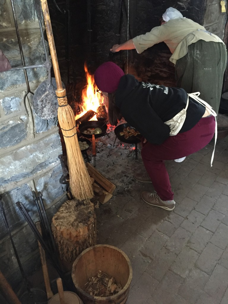 Nicole flipping meat balls over an open hearth (a 1930s-era reconstruction) at Landis Valley, February 2015