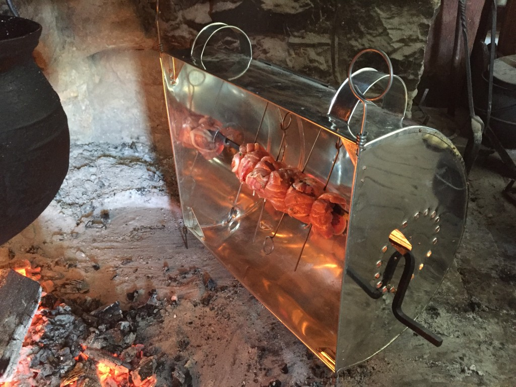Roasting pork-wrapped bacon in a reflector over at Landis Valley, February 2015