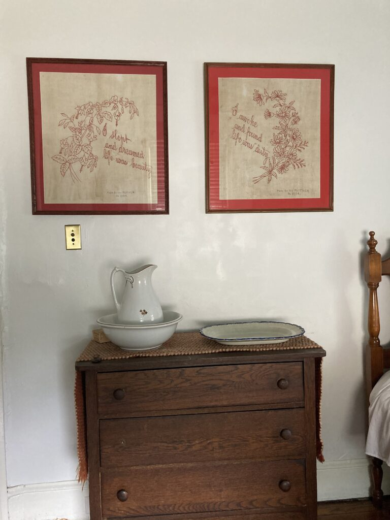 This is a color photograph of two pieces of framed needlework on a white wall. They are having above a dresser that has a ceramic wash bowl and basin on it as well as blue and white platter.